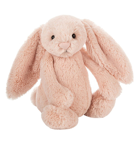 Medium pink blush bunny with floppy ears and black plastic pellet eyes placed on a table.