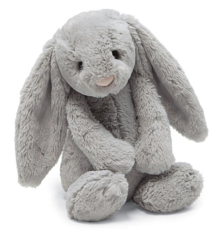 Medium grey bashful bunny with a pink nose and black plastic pallet eyes and floppy ears sitting on a table.