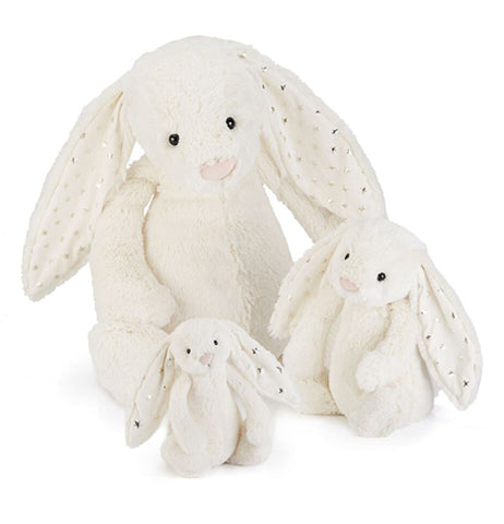 Large, medium, and small white bashful twinkle bunnies with silver stars in their ears sitting next to each other.
