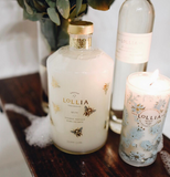"The ""Wish"" Candle sits on a wooden table next to some bath soap and a tall bubble bath bottle."