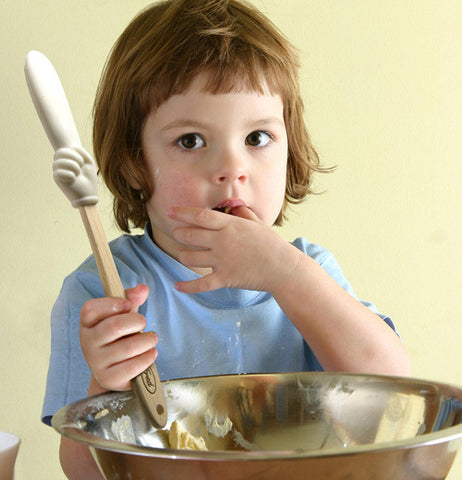 Girl holding the batter finger spatula over a mixing bowl while eating what's in the bowl