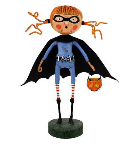 This figurine is of a little girl wearing a blue suit with a black bat wing shaped cape and holding A Jack-O-Lantern basket.