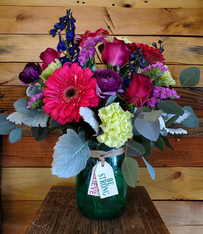 "A multi-colored bouquet of flowers sits in a transparent green mason jar. There are red, light yellow, blue, and purple flowers. Twine string is wrapped around the jar, and a tag says ""Be strong"" in green lettering."