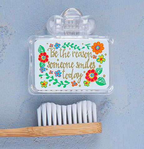 its a tooth brush cover that says Be The reason Someone Smiles Today surrounded by flowers with a tooth brush