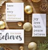 "Three Signs lay on a wooden table surrounded by gold Christmas ornaments. The signs say ""Have a very Merry Christmas"", ""Joy, Love, Faith, Peace, Believe"", and ""This House Believes"""