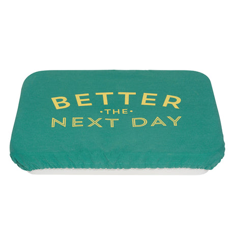 "Green polyurethane, cotton, and polyester baking dish cover that says ""Better the Next Day"" in yellow covering a pan."