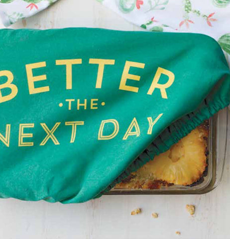 "Green cotton, polyurethane, and polyester baking dish cover saying ""Better the Next Day"" in yellow with corner pulled up on lower right of baking pan."