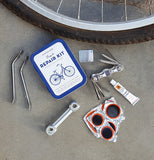 A bicycle tire lies on a sidewalk with the bicycle repair kit and its contents next to it.