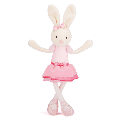 A stuffed white rabbit wearing a pink tutu, ballerina shoes and ribbon on top of her head. Standing against a white background with legs crossed and arms out to the side.
