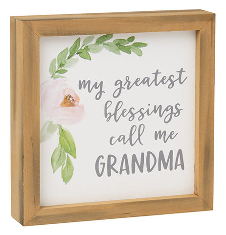 White framed box sign with a green and pink flower drawing that says My Greatest Blessings call me Grandma.