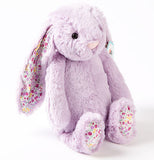 A purple Medium Blossom Jasmine Bunny with pink and purple flowers on its ears and the undersides of its feet sits.