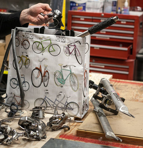 Shopping bag with bicycle print in a work space filled with tools with man pulling out part.