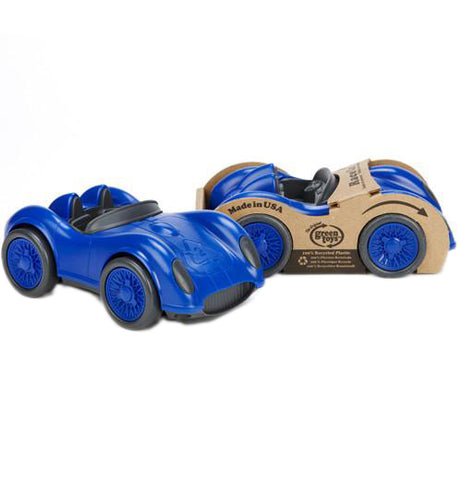 a dark blue race car with black wheels and accents alongside the same car in its original packaging