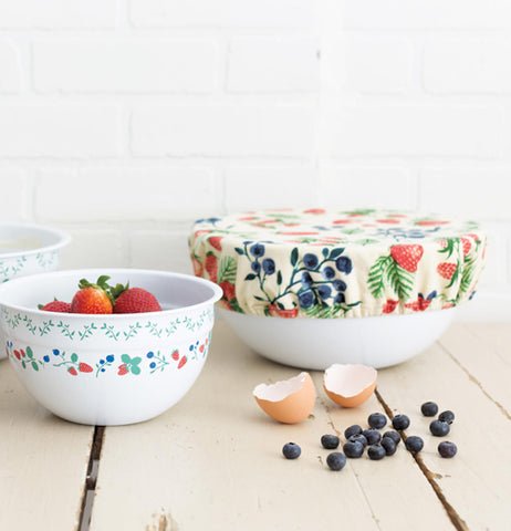 The strawberry and blueberry designed cloth top is shown covering a white bowl on a table.