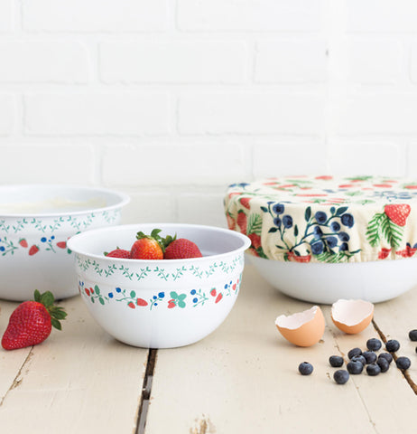 These berry patch bowls are sitting on a table with fruit in the bowl.