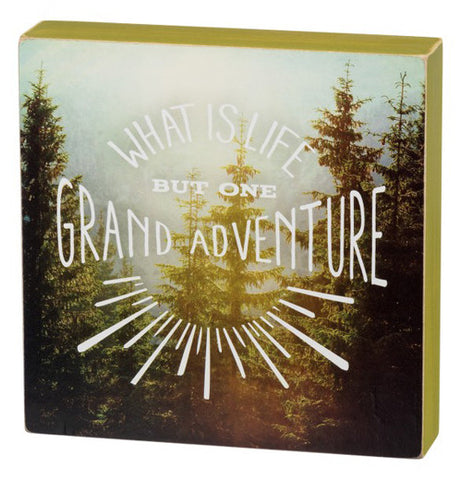 "Box sign with ""What is Life But One Grand Adventure"" printed over a landscape picture in the background."