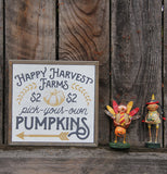 a box sign with happy harvest farms, pick-your-own, and Pumpkins sitting against a wood background with two figurines, on of a kid in a turkey costume and the other of a girl in a native american costume.