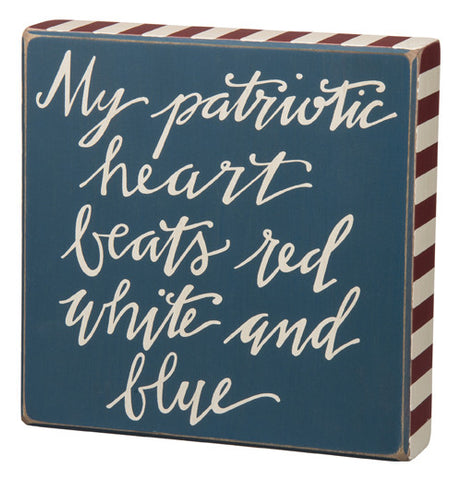 "This box sign says ""My Patriotic Heart Beats Red White And Blue."" the sign is blue with red and white stripes around the edge and the words are white."