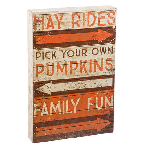 An orange, brown, off-white wooden sign with the phrases, hay rides, pick your own pumpkins and family fun