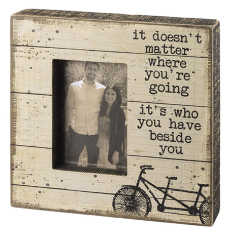 "An off-white wooden box sign with the phrase ""It doesn't matter where you're going it's who you have beside you"" above a two person bicycle"