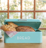 Turquoise Bread Box filled with different kinds of bread and sitting on a wood counter with a glass paneled window in the background.