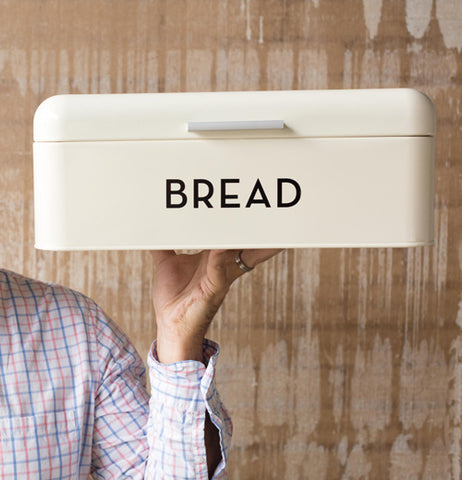 A Cream Colored Bread Box with the black lettering Bread is being held in the air by someone in a white cross stitch shirt