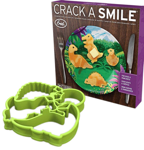 "Four green dinosaur pancake molds sit outside the package with the picture of a plate, dinosaur shaped pancakes and a fork and knife with text at the top that reads ""Crack a Smile"""