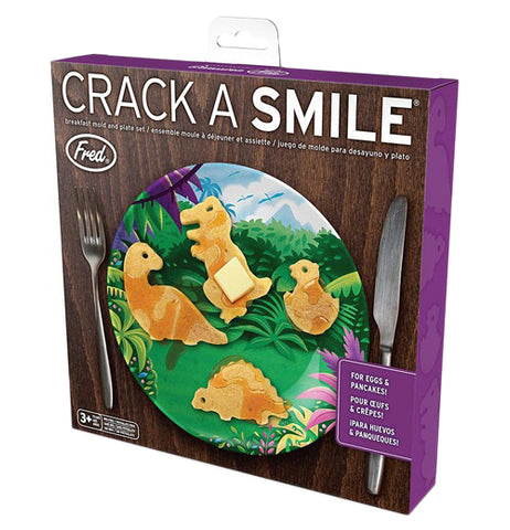 "The box of the Crack A Smile ""Dinosaur"" Breakfast Set has the picture of four dinosaur shaped pancakes, a plate, fork and knife."