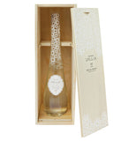 The clear bottle of bubble bath with a floral top is sitting delicately inside of its custom made wooden box.