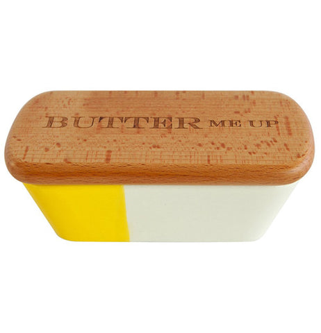 "A butter tub 1/3 is yellow and rest is white with a wooden lid that says ""Butter me up""."