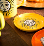 The yellow coaster with a white faced sun in the center is shown sitting on a wooden table next to a mug with the same design.
