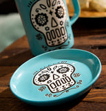 "The Cuppa Color ""Blue Skull"" Coaster sits on the wooden table with the ""Blue Skull"" mag."
