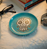 "The Cuppa Color ""Blue Skull"" Coaster sits with the glasses, the textbooks, and the wristwatch on the mattress."