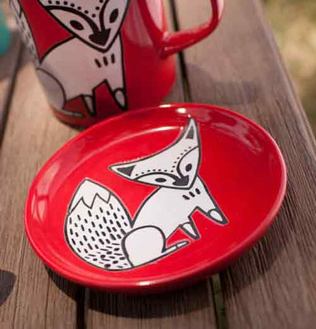 "Round ""Red Fox"" coaster with white and black fox design on brown wood table laying next to ""Red Fox"" mug with same fox design."