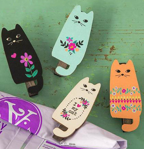 Set of 4 Cats Magnet Clips Comes with Black, White, Orange and Blue and have different decorative flower designs without the container lying on the green background