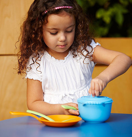 little girl playing with the blue pot and skillet with the yellow spatula
