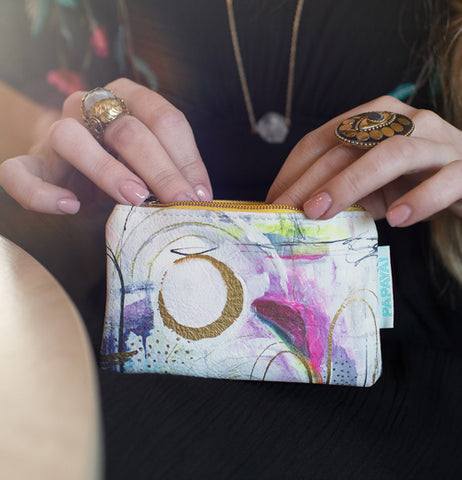 "A woman holds the ""Brushstrokes"" Coin Purse on her lap with her two hands."