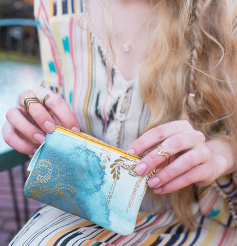 "A lady holding a ""Catalina Watercolor"" Coin Purse in her lap."