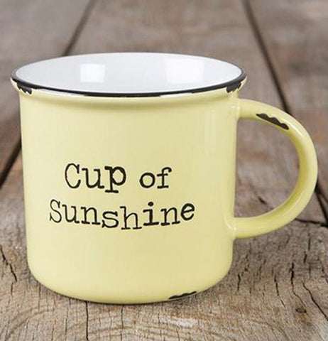 "The yellow mug with the words, ""Cup of Sunshine"" in the middle of its outside is shown sitting on a wooden table background."