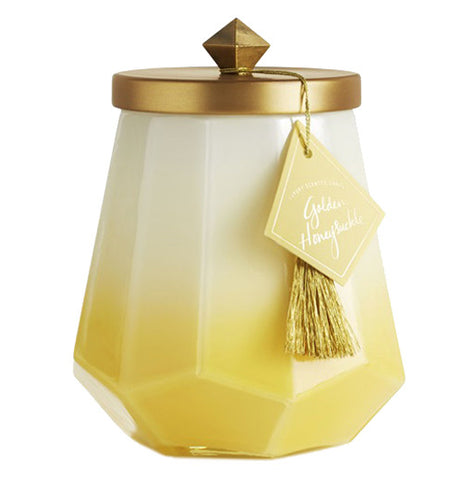The candle is in a glass container that fades from white at the top to yellow at the bottom and a gold lid with a gold tassel hanging from the lid.