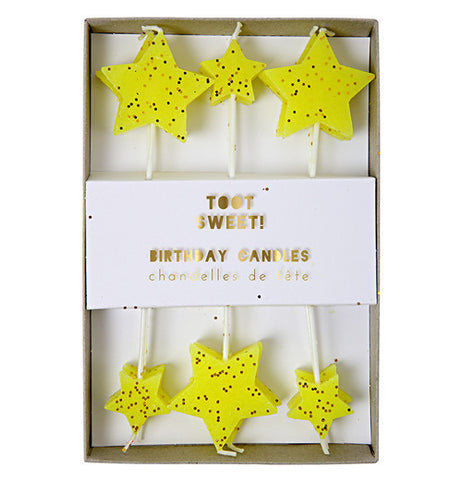Candles with yellow stars at the top and they are different sizes.