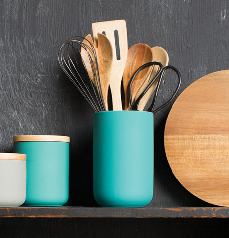 The turquoise canister is shown sitting on a shelf with different kitchen spoons in it. To the left is a smaller turquoise canister and a smaller gray one. On the right is a circular cutting board.