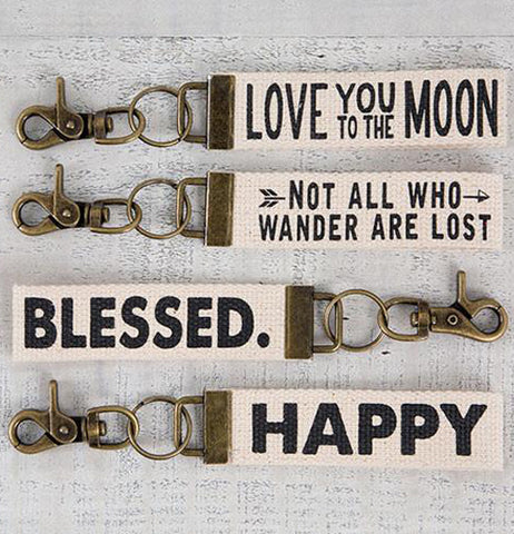 "A few different key fobs are shown, all with white banners sporting different words. The top banner says, ""Love You to the Moon"", the second says, ""Not All Who Wander Are Lost"", the third says, ""Blessed"", and the fourth says, ""Happy""."