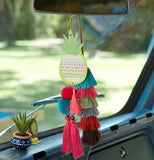 "The ""Pineapple Sweet"" Car Air Freshener hangs from the rearview mirror of a car along with a bunch of colorful tassels and a mini cactus in a colorful planter sits on the dash."