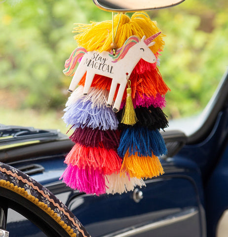 The unicorn air freshener is shown hanging with some red, yellow, plum, and pink tassels from a car's rear-view mirror.