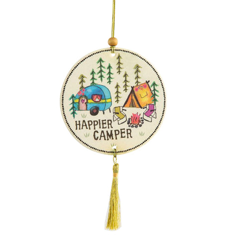 "This white air freshener has a design of a blue trailer, an orange tent, and a yellow chair and pink chair on either side of a camp fire. The whole campsite is surrounded by pine trees, and the words, ""Happier Camper"" are at the bottom in brown lettering."