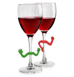 two half full wine glasses, one has the green charades wine marker on it the other has the red.