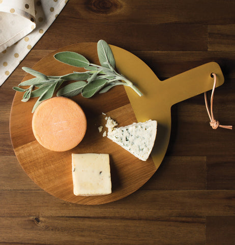 Cheese board with three different kinds of cheese and a sprig of sage.
