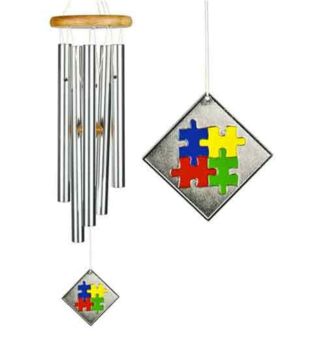 These silver colored chimes hang from a wood colored top with blue, yellow, red and green puzzle pieces.
