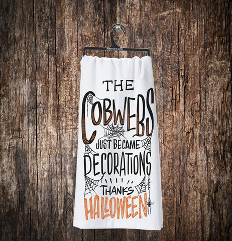 "The white towel with the words, ""The Cob Webs Just Became Decorations Thanks Halloween"" is shown hanging on its black hanger against a wooden background."